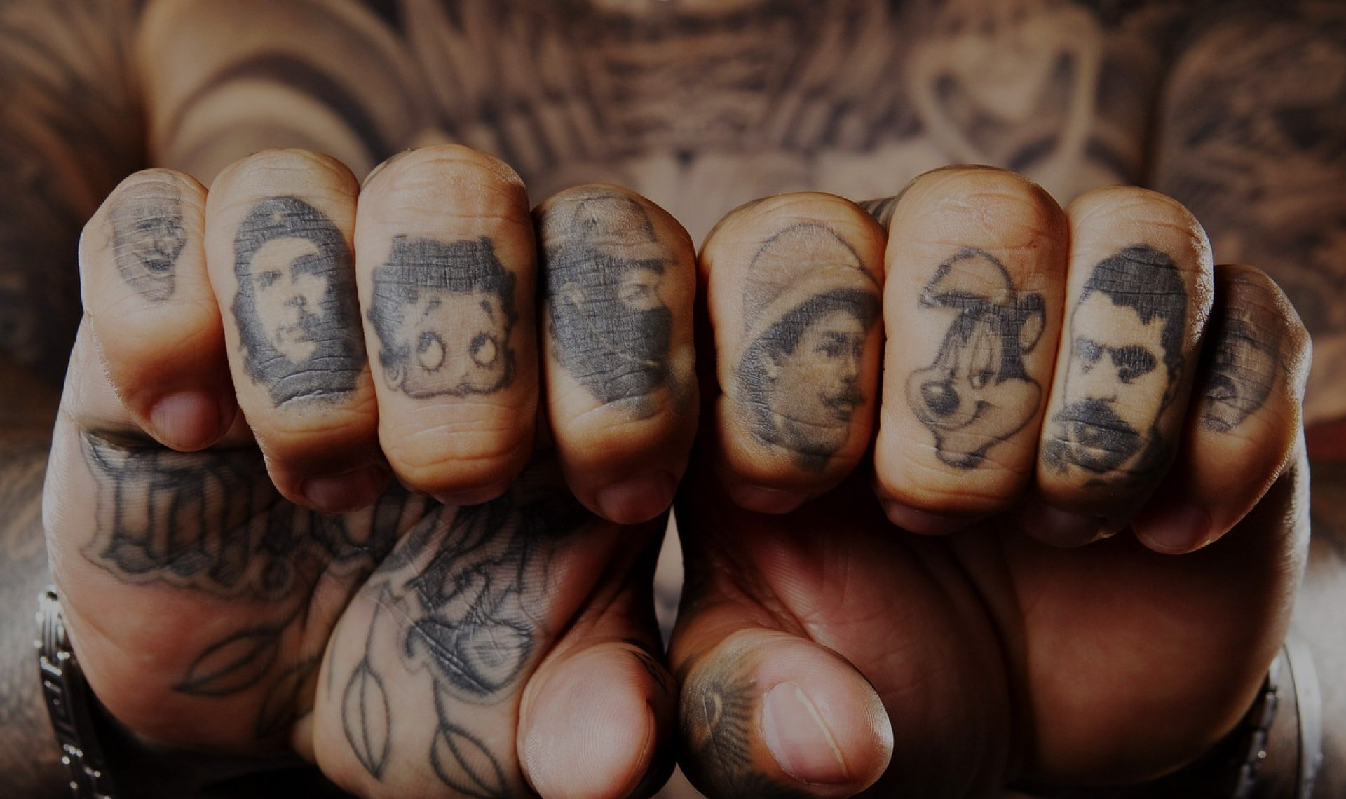 amous faces tattooed across a mans knuckles